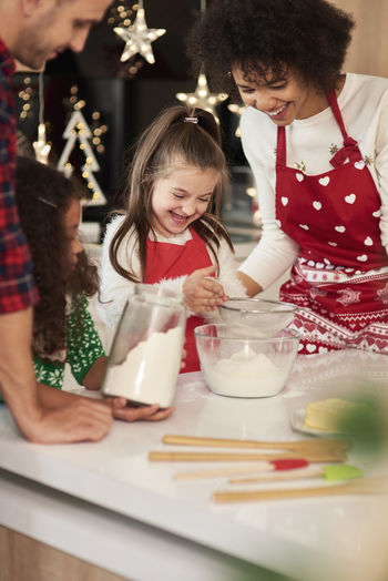 Girl with parents and sister preparing food during christmas in kitchen at home