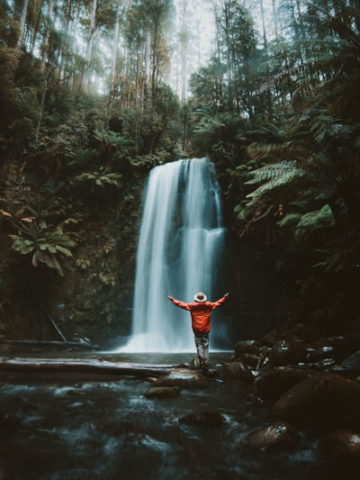 Arms Outstretched Arms Raised Beauty In Nature Flowing Water Forest Freedom Human Arm Land Leisure Activity Limb Long Exposure Motion Nature One Person Outdoors Plant Rainforest Real People Scenics - Nature Standing Tree Water Waterfall