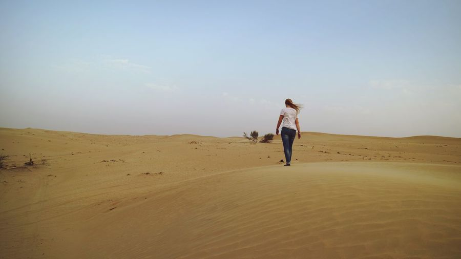 Lifestyles Real People Full Length Leisure Activity Sand Rear View Outdoors Nature Dubai Clear Sky Desert Day Sky Women Arid Climate One Person Landscape Beauty In Nature Sand Dune Young Adult Lost In The Landscape