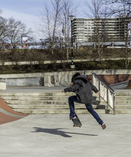 Rear View Of Man Skateboarding In Park