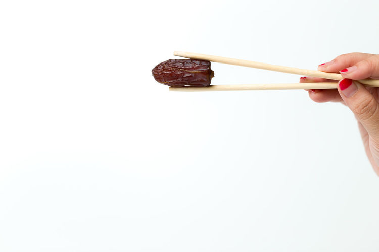 A woman hand hold a dates usinga chop stick isolated over white background. Antioxidant Berry Brewing Calories Cooking Dates Dessert Diet Energy EyeEmNewHere Food Freshness Fruit Grape Healthy Healthy Eating Natural Nature Nutrition Organic Restaurant Snack Sugary Sweet Vegetarian
