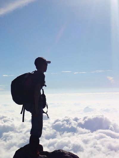Side view of man with backpack standing on cliff against sky