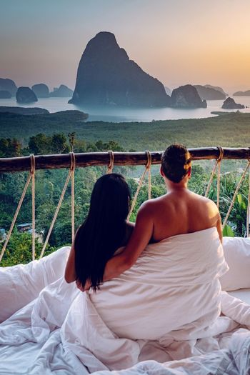 Rear view of couple covered under blanket while sitting against mountain during sunset