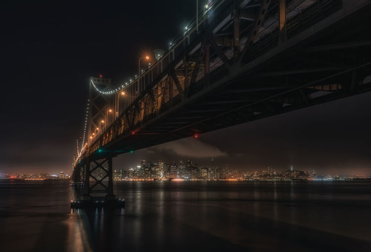 Low angle view of illuminated bay bridge over river against sky at night