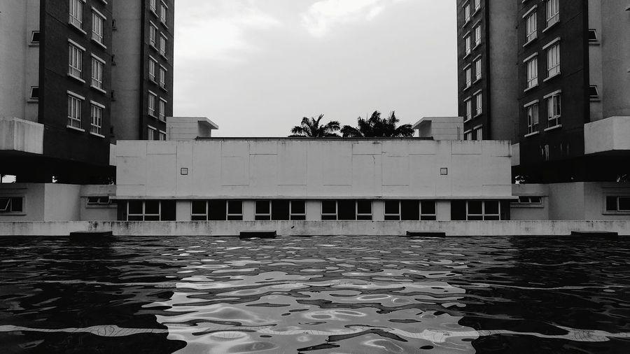 Buildings by swimming pool in city against sky
