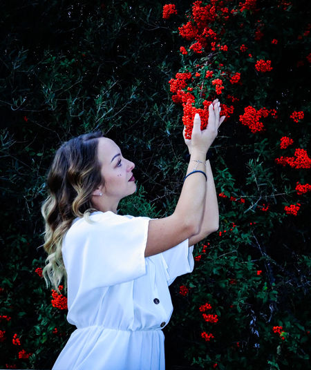 Beautiful woman standing by red flowering plants