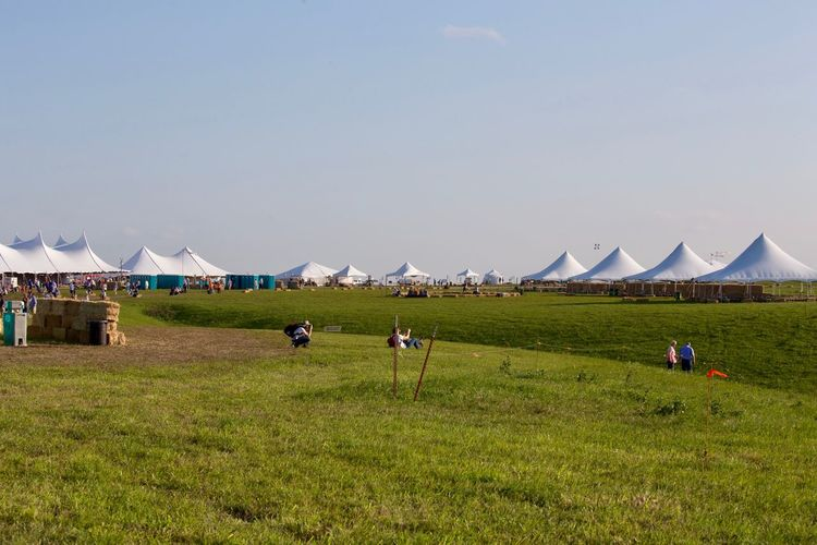 Tent Set-up for Symphony in the Flint Hills by the Kansas City Symphony Symphony Orchestra Annual Event Outdoor Concert Venue Field Outdoors Grass Tent People Nature Day Real People Rural Scene Sky Beauty In Nature
