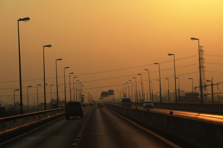 Traffic on highway at sunset