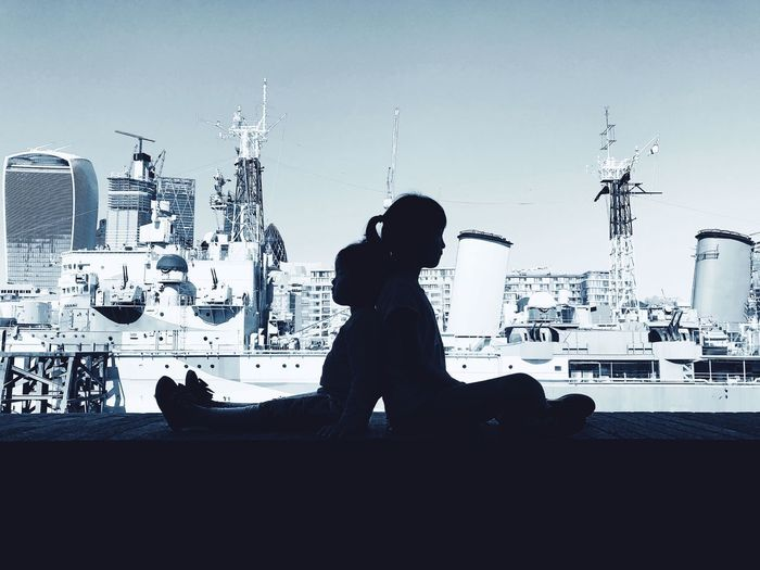 Side view of silhouette man sitting in city against sky