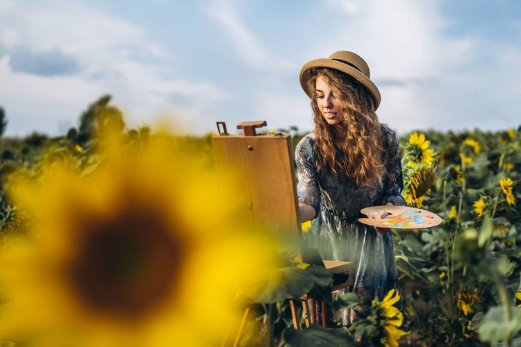 Woman standing by flowering plants on land against sky
