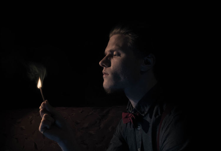 Young Man Igniting Matchstick In Darkroom