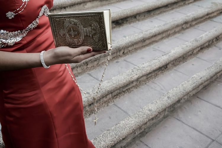Close-Up Mid Section Of Woman Holding Rosary And Holy Book