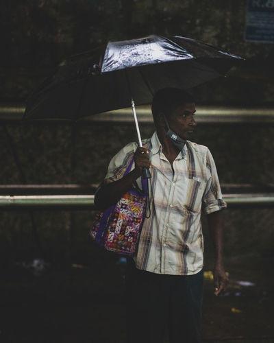 Man holding umbrella while standing during rainy season