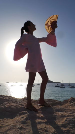 Full Length Of Young Woman With Hand Fan Standing On Seashore Against Clear Sky