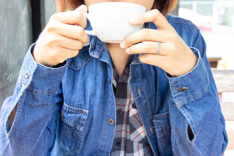 asian woman wearing blue jean shirt and drinking a hot coffee in the morning One Person Holding Real People Casual Clothing Midsection Drink Coffee - Drink Cup Coffee Food And Drink Mug Front View Denim Lifestyles Coffee Cup Refreshment Women Leisure Activity Human Hand Jeans Hand Drinking Tea Cup
