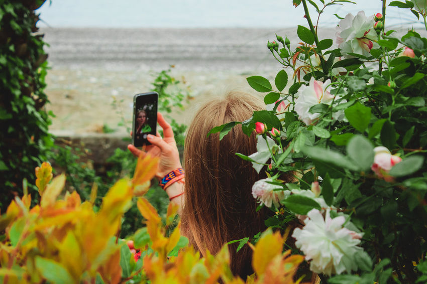 Beauty In Nature Cellphone Communication Day Flower Growth Holding Leisure Activity Mobile Phone Nature One Person Outdoors Photo Messaging Photographing Photography Themes Plant Portable Information Device Real People Screen Sea Smart Phone Technology Using Phone Wireless Technology Women