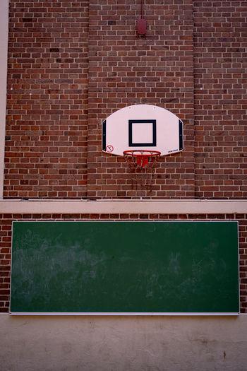 Close-up of basketball hoop against brick wall