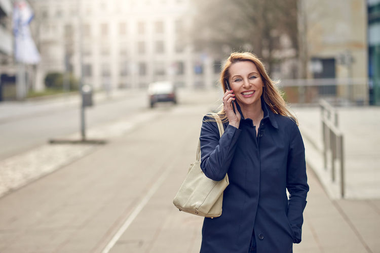 Attractive blond woman chatting on her smartphone Copy Space Happiness Morning Architecture Beautiful Woman Business Person Businesswoman City Communication Conversation Evening Focus On Foreground Middle-aged Mobile Phone One Person One Woman Only Outdoors Smiling Spring Successful Technology Telephone Using Phone Walking Wireless Technology