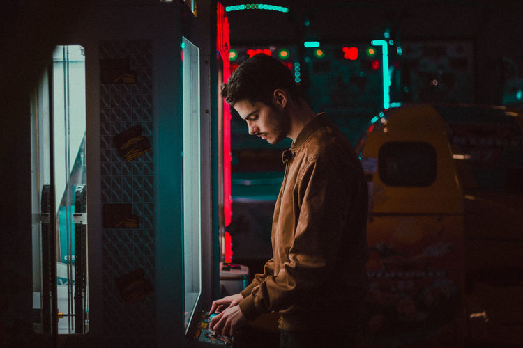 Young Man Playing On Arcade Machine