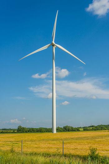 Wind turbine on field against sky