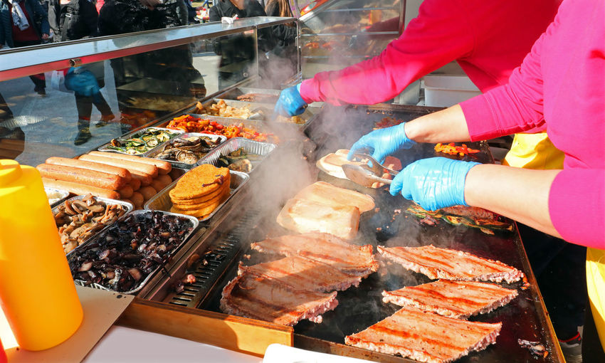 Cook with gloves while cooking sausages in the street food stall