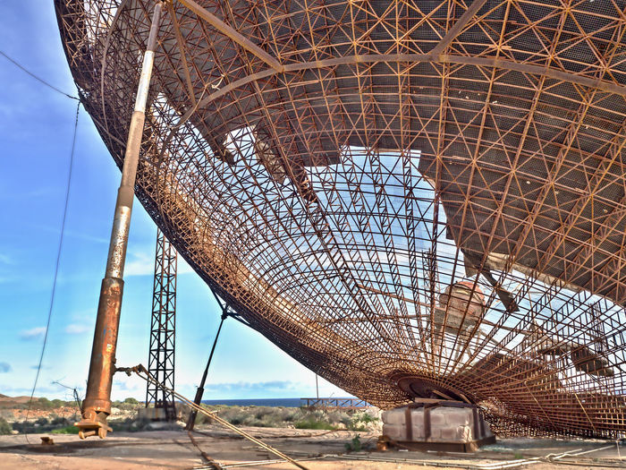 Detail of a completely destroyed and broken old, very large satellite dish amidst a barren sand landscape in the south of Tenerife. The iron frame is now visible Detail Broken Destroyed Satellite Dish Large Dish South Of Tenerife Island Canarias Iron - Metal Ferry Scaffolding Abandoned Places Rusted Metal  Bowl Built Structure Architecture Day No People Metal Sky Low Angle View Travel Tourism Nature Outdoors Pattern Grid