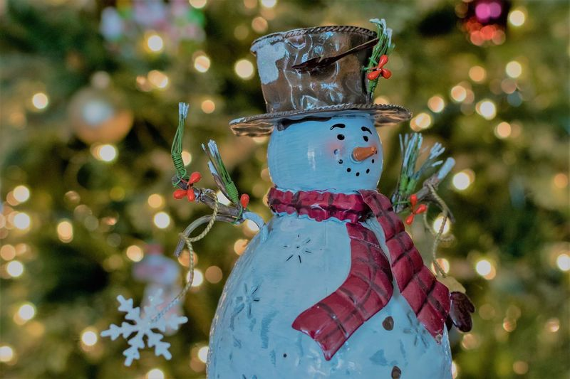Close-Up Of Snowman Against Illuminated Christmas Tree