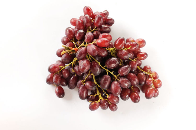 Close-up of red berries against white background