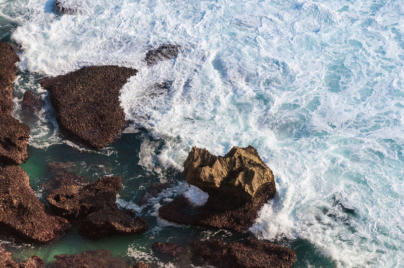 Rocks in the ocean, viewed from above Aerial View Aquatic Sport Beach Beauty In Nature Breaking Day High Angle View Hitting Land Motion Nature No People Outdoors Power In Nature Rock Rock - Object Rock Formation Sea Solid Splashing Sport Water Wave