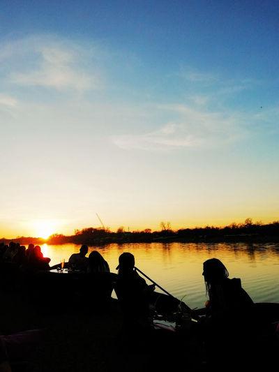 Silhouette people sitting on shore against orange sky
