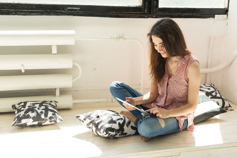 Young woman using phone while sitting on floor