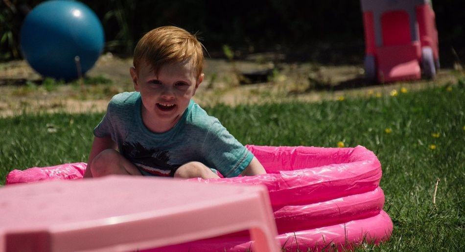 Portrait Of Redhead Boy Sitting In Pink Wading Pool At Back Yard