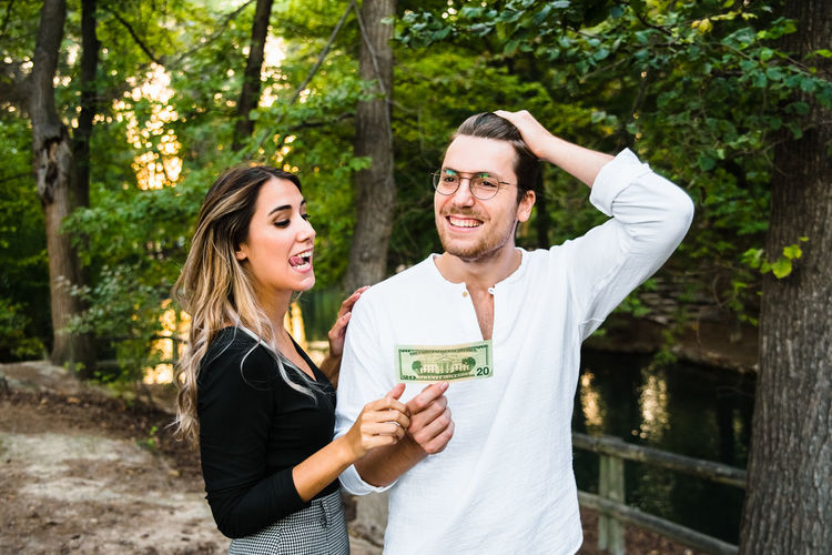 Smiling young couple standing against trees
