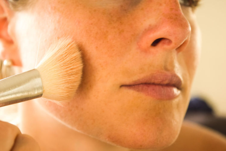 Close-up of woman applying make-up with brush
