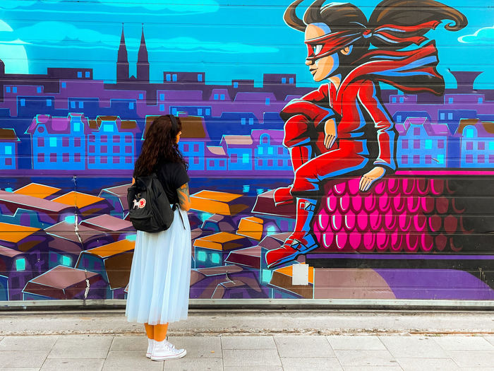 Rear view of woman standing against multi colored building