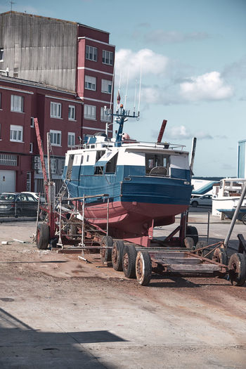 Boats moored on shore against buildings in city