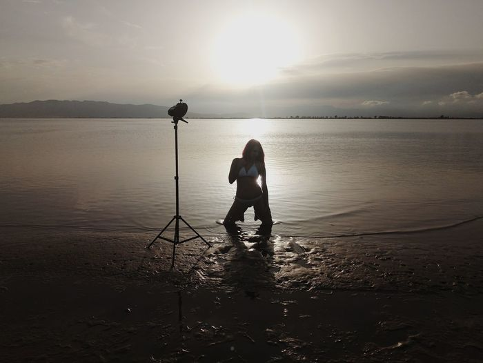 Female model kneeling at lakeshore against sky during sunset