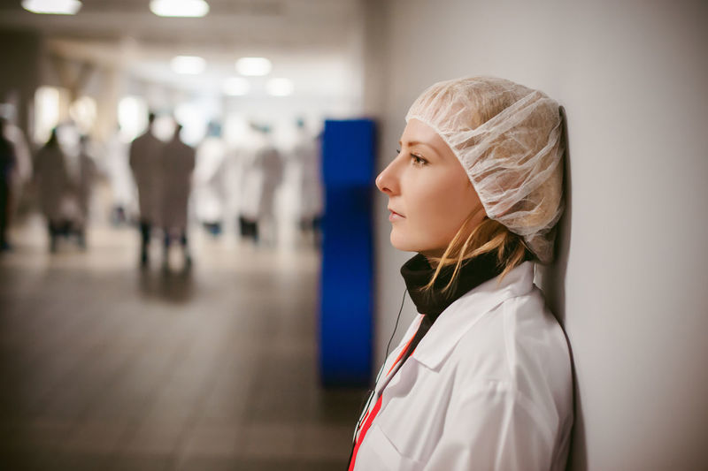 Side View Of Female Doctor Wearing Surgical Cap While Standing Against Wall In Hospital