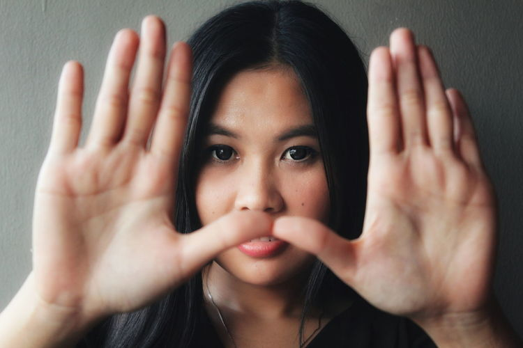 Portrait of beautiful young woman showing stop gesture against wall