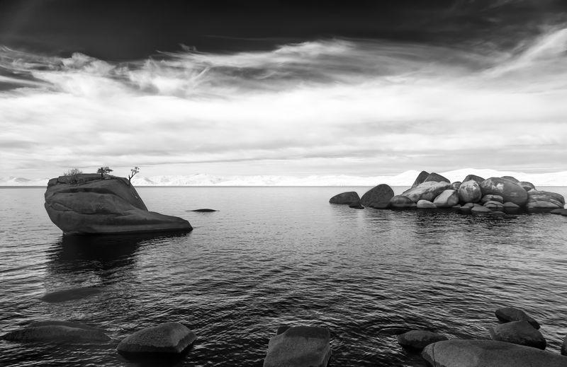 Rocks floating on sea against sky