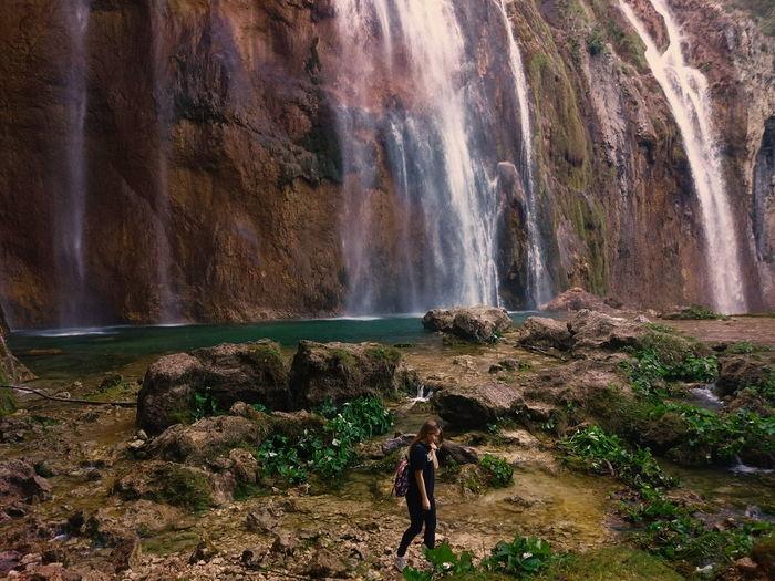 Side view of woman walking against waterfall