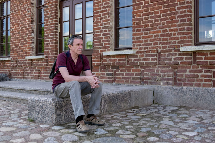 Full length portrait of man sitting against brick wall