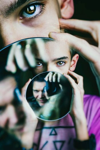 Close-Up Portrait Of Boy Holding Mirror With Reflection
