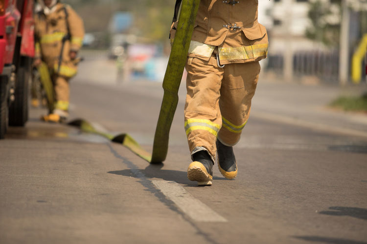 Low section of firefighter arranging fire hose on road