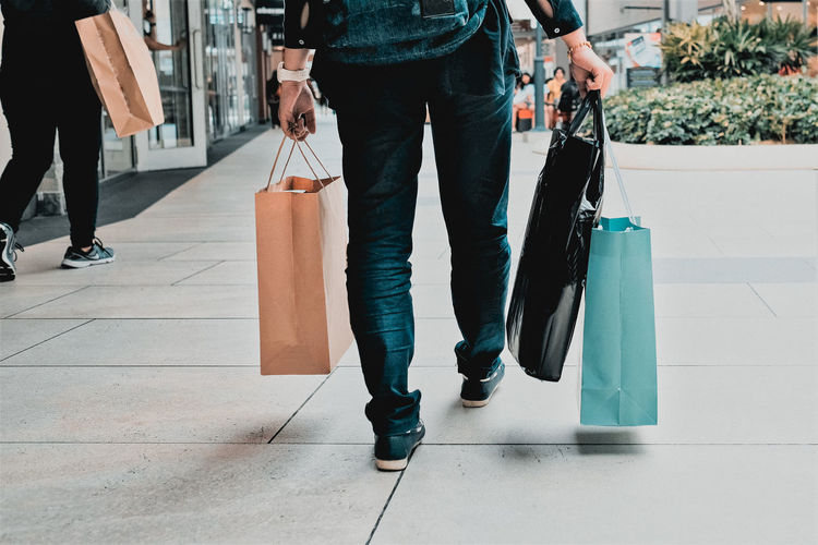 Shopping Shopping Spree Adult Bag Casual Clothing Consumerism Footpath Human Leg Incidental People Jeans Leisure Activities Leisure Activity Lifestyles Low Section People Real People Retail  Shopping Shopping Bag Shopping Mall Walking Women