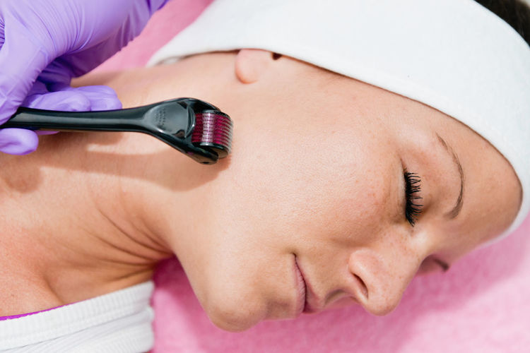 Close-Up Of Woman Lying Down With While Beautician Using Cosmetic Roller On Face At Spa