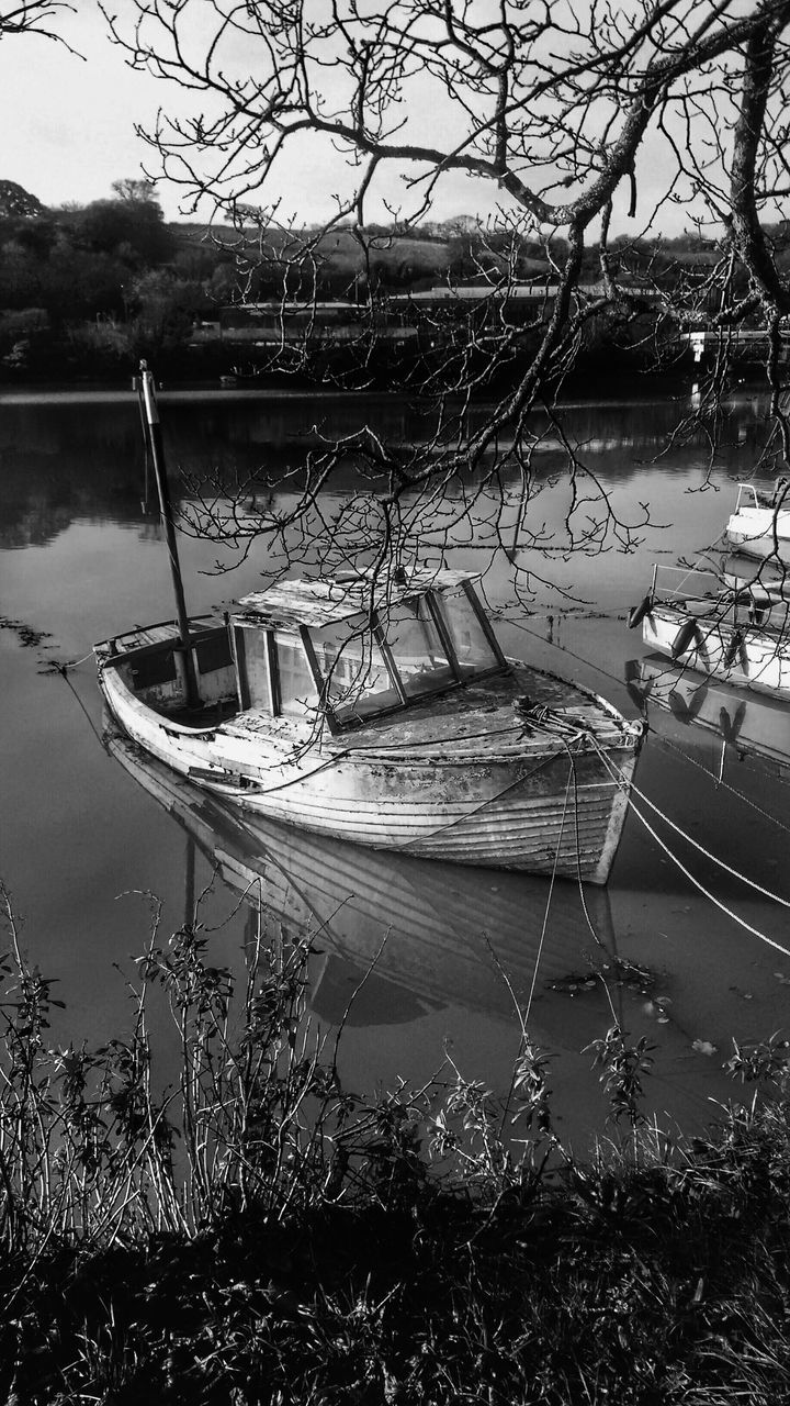 nautical vessel, moored, transportation, mode of transport, boat, water, tree, nature, lake, outdoors, no people, rowboat, day, tranquility, waterfront, branch, sky, beauty in nature