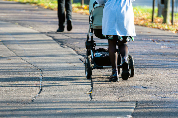 Low section of woman walking with baby stroller on road