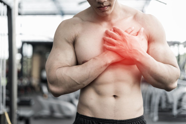 Midsection of shirtless muscular man suffering from chest pain in gym