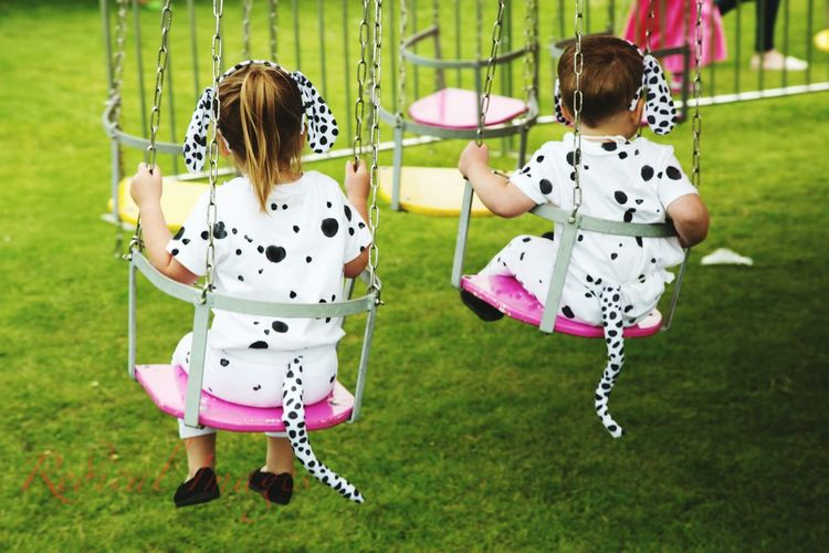 Rear View Of Girls In Dalmatian Dog Costumes Sitting On Swing At Park
